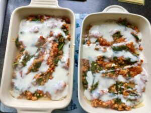 Lasagne assembly with white sauce on top of ragu.