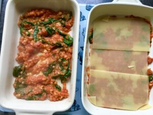 Lasagne assembly with pasta sheets on top of ragu.