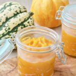 Pumpkin puree in a jar with pumpkins behind it.