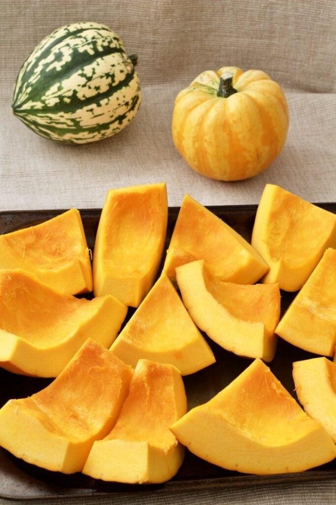 Pumpkin chunks on a baking tray.