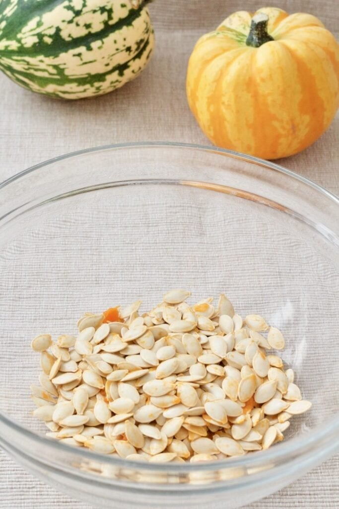 Raw pumpkin seeds in a bowl.