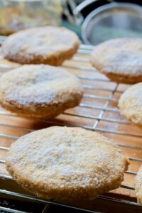 Mince pies sprinkled with icing sugar on a cooling rack.