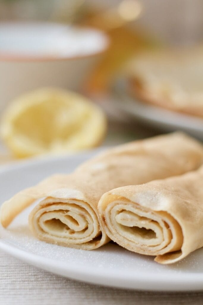 Close up of two rolled up pancakes.