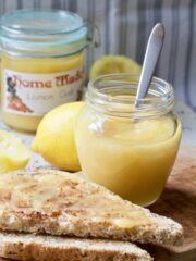 Lemon curd in a jar with a spoon and on toast.