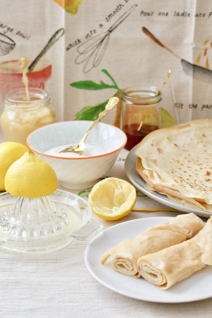 Pancakes spread on the table with lemon juice, sugar, jam, lemon curd.