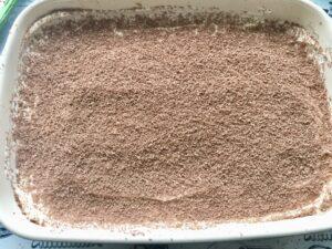 Easy Eggless Tiramisu - grating of chocolate on the first layer of mascarpone cream