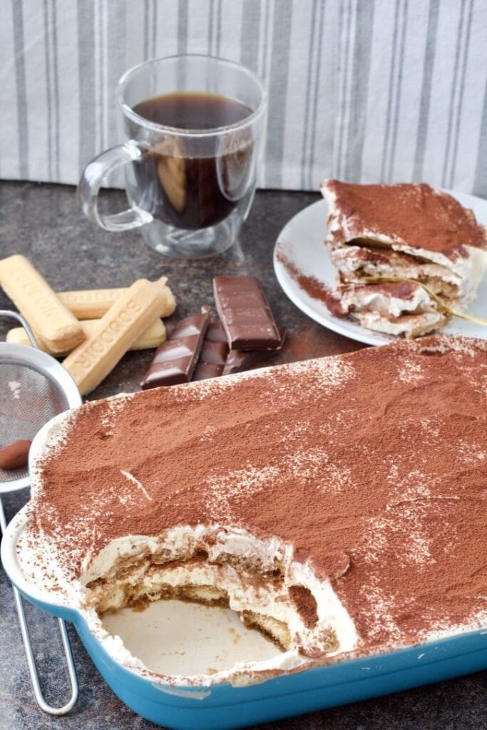 Easy Eggless Tiramisu - dish with tiramisu, one portion on a plate, cup of black coffee, chocolate pieces and lady fingers biscuits