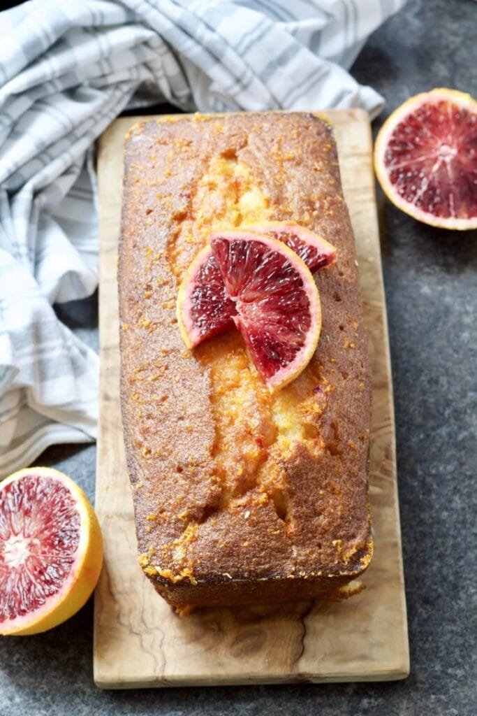 Easy Blood Orange Drizzle Cake on a board decorated with blood orange slices.