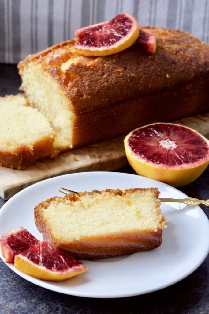 Slice of cake on a plate and loaf in the background.