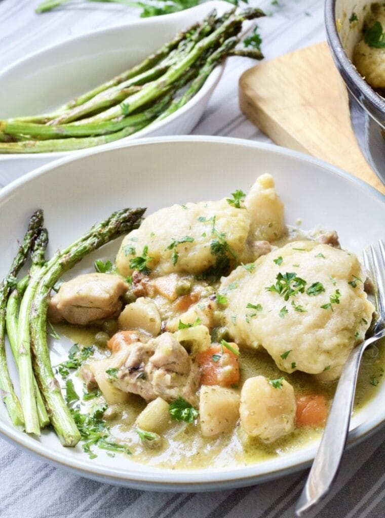 Wild Garlic Chicken Stew with Cheesy Dumplings on a plate with asparagus
