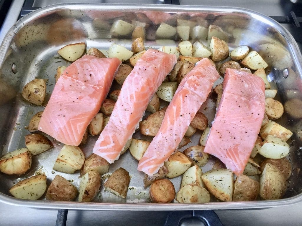 Roasting tray with pre-baked new potatoes and salmon fillets on top.