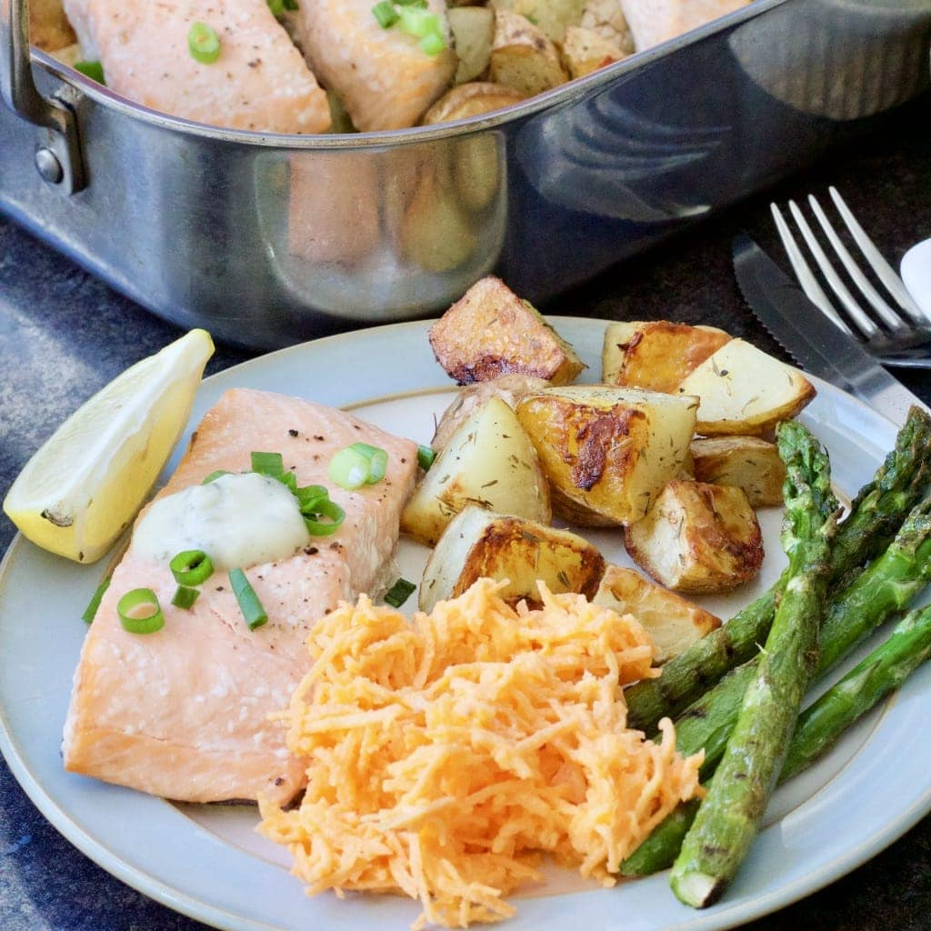 Fish, potatoes, carrot salad & asparagus on a plate.