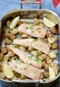 Roasting tray with potatoes, salmon & lemon wedges.