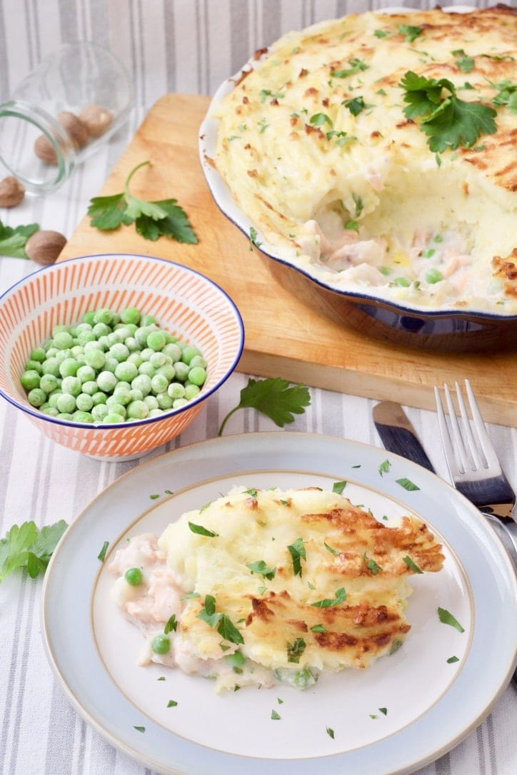 Fish pie in a dish and on a plate with bowl of peas.