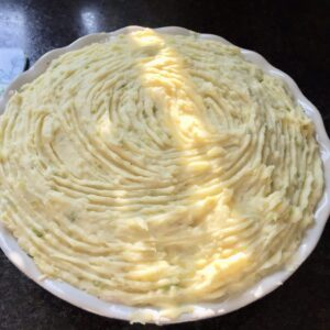Mashed potato covered pie in a dish.