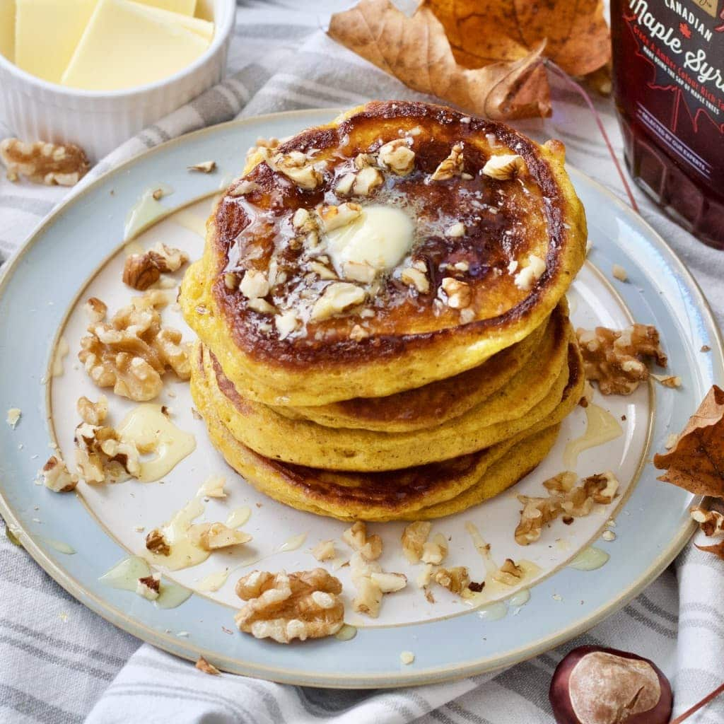 Plate with pancake stack, walnuts and melting butter on top.