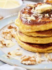 Stack of pumpkin pancakes with walnuts & butter.