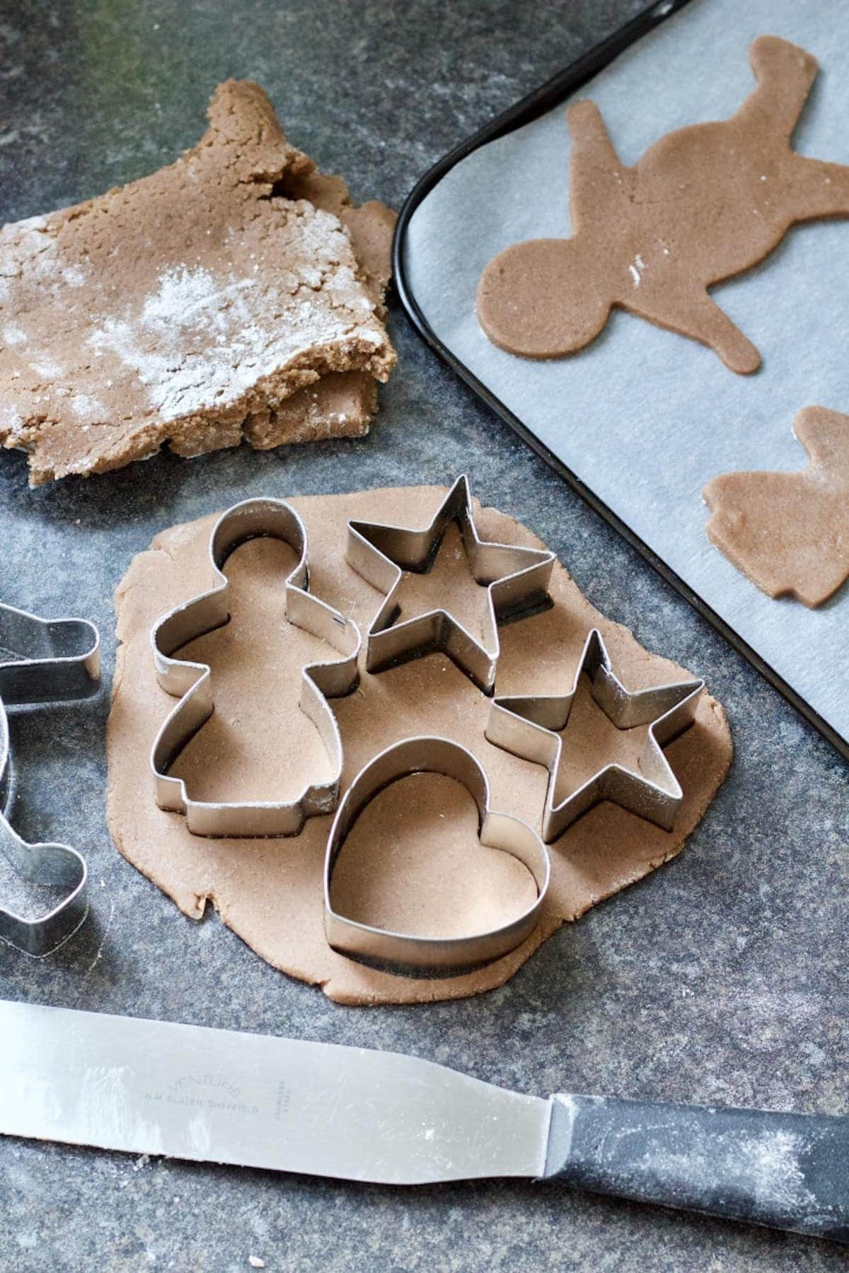 Biscuits being cut out of dough with cutters.
