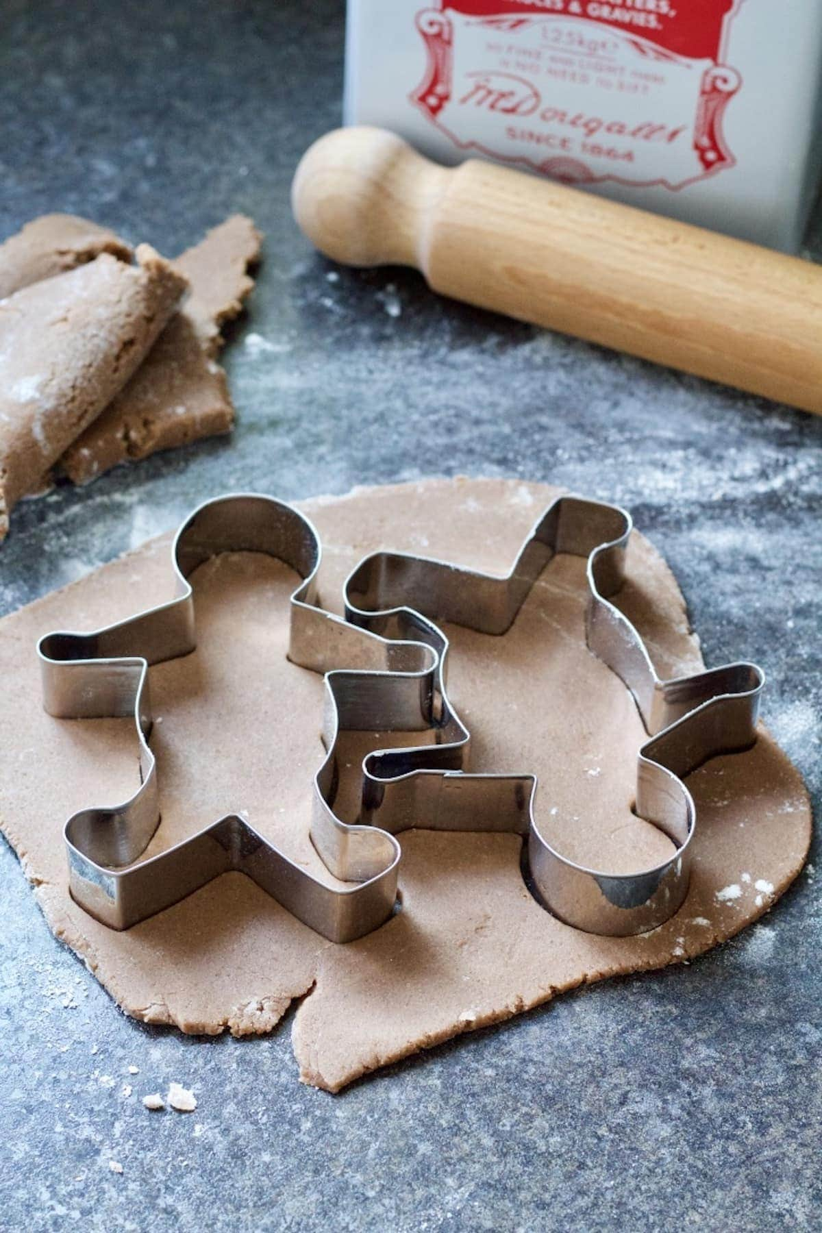 Two gingerbread men cutters on top of rolled out dough.