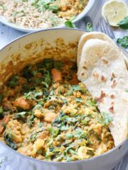 Cauliflower and lentil curry in a pot with some flat bread.
