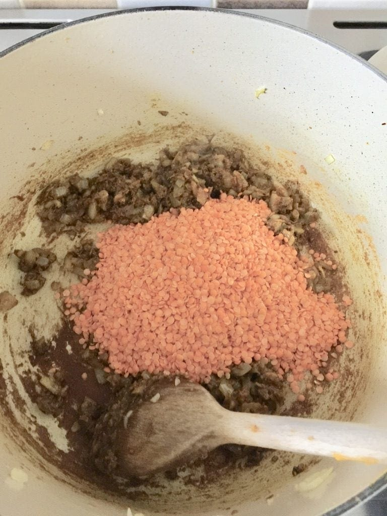 Lentils being added to the curry paste and onion mixture.