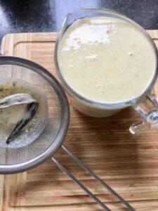 Vanilla Crème Brûlée - sieved custard mixture with discarded vanilla pod on a sieve