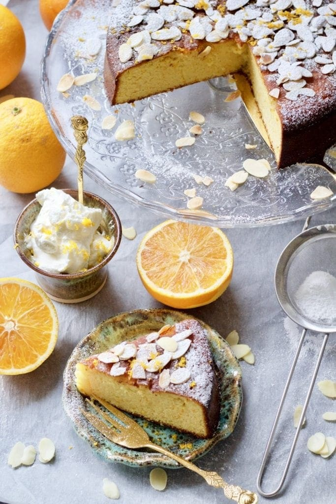 Gluten-Free Orange and Almond Cake sliced on a plate and cake on a stand