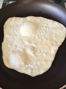 Easy Flatbread (No Yeast) in the frying pan with bubbles rising to the surface