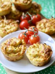 Cheesy Carrot & Courgette Savoury Muffins on a plate with cherry tomatoes