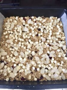 Flapjacks in a baking tin with scattered almonds & white chocolate chips