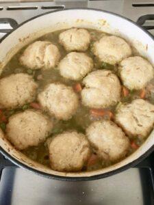 Wild Garlic Chicken Stew with Cheesy Dumplings in a pan
