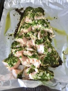Baked pesto salmon flaked into pieces