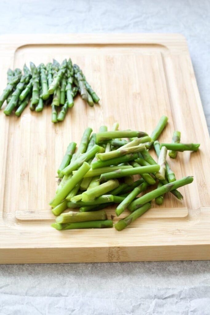 Asparagus pieces on a chopping board,