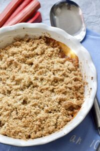 Rhubarb crumble in a dish with serving spoon.
