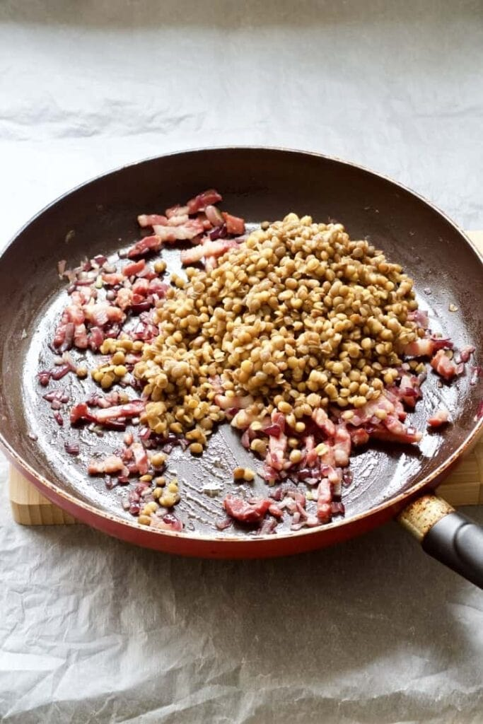 Green lentils with bacon and onion in a pan.