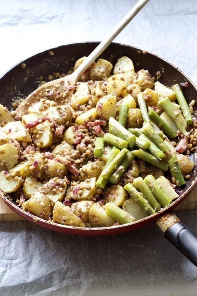 Asparagus chunks with potatoes and lentils in a pan.