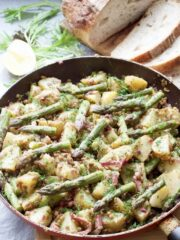 Salad in a pan with asparagus tips on top.