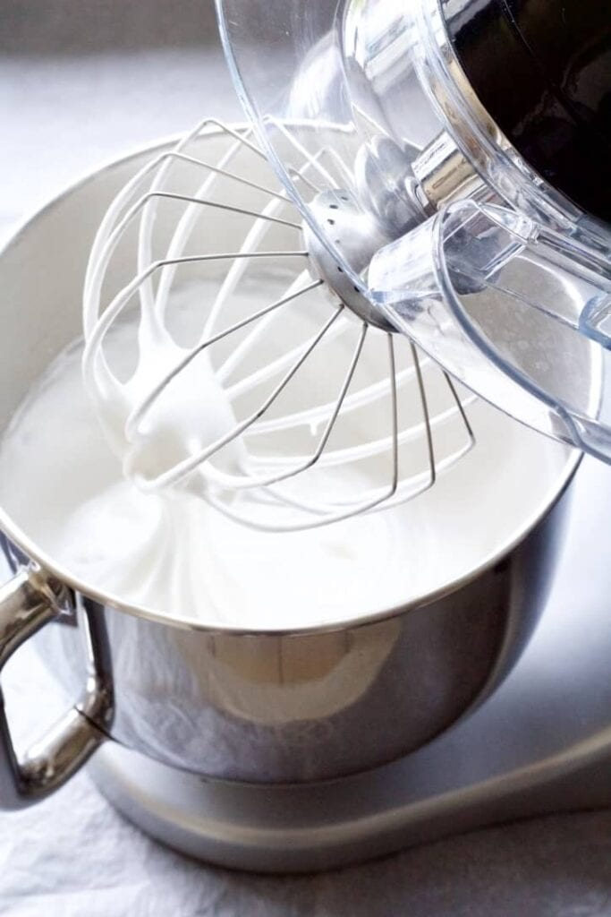 Silky beaten egg whites in a bowl of standing mixer.
