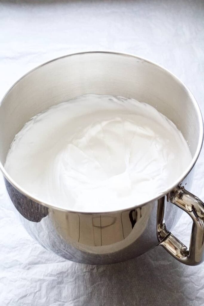 Egg whites beaten to stiff peaks in a bowl.