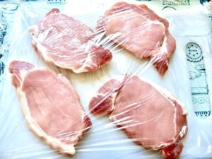 Pork chops on cutting board covered with cling film.