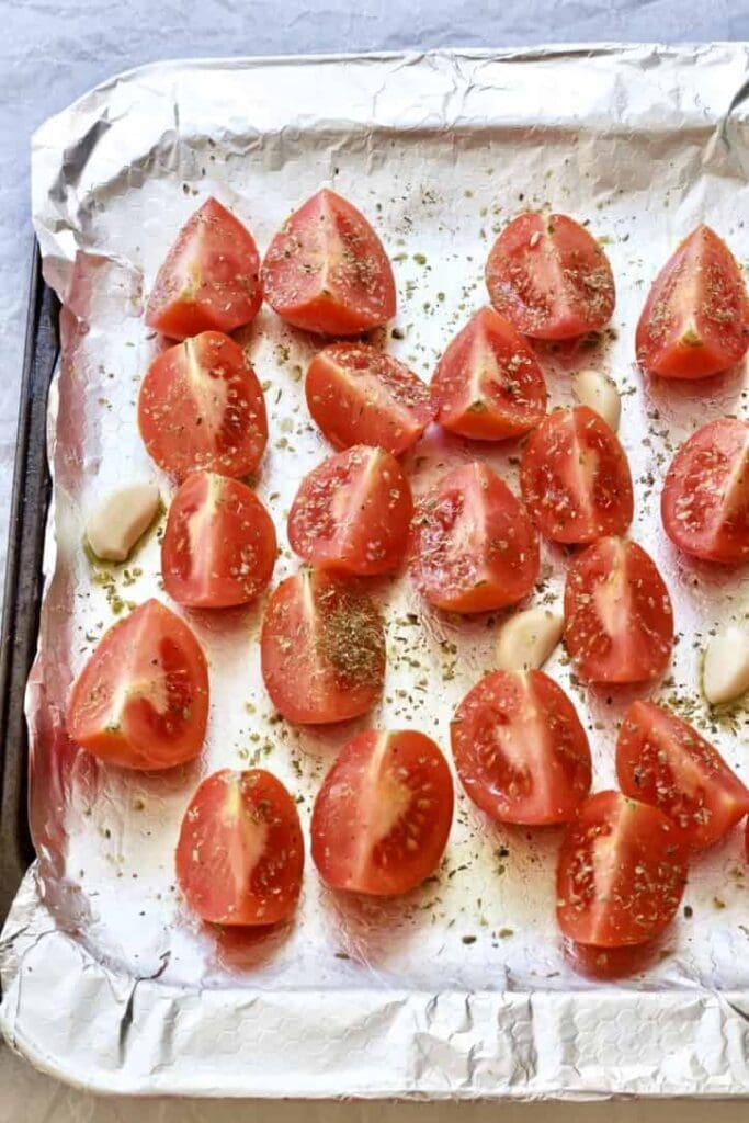 Quartered tomatoes on a baking tray with garlic.