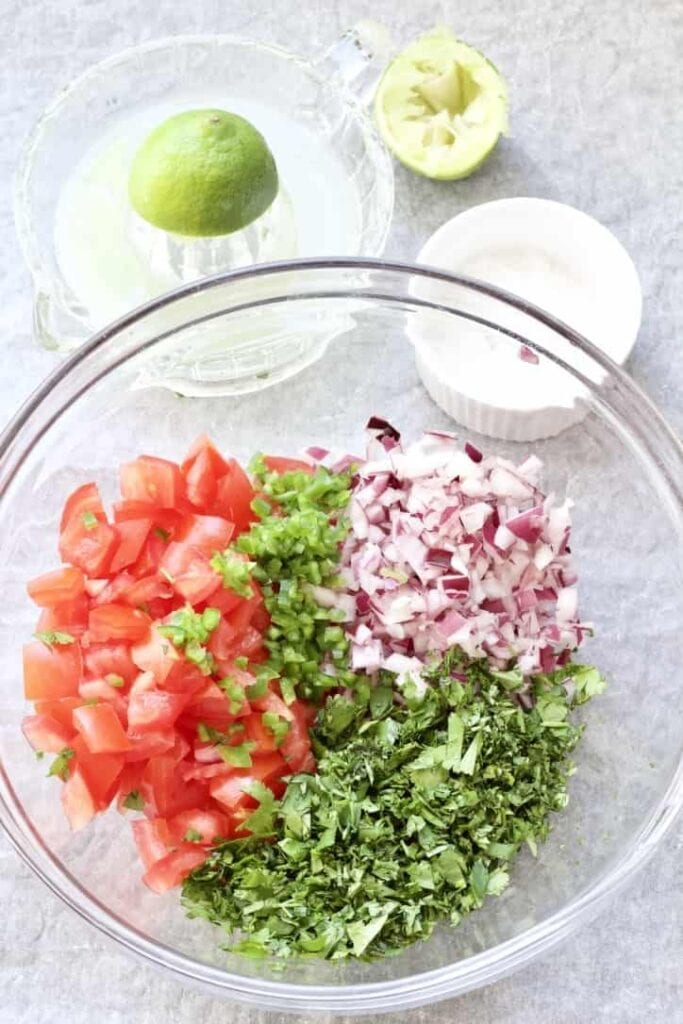 Chopped tomato salsa ingredients in a bowl.