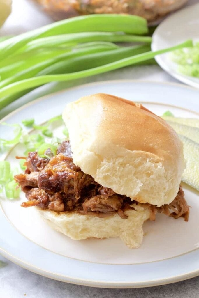 BBQ pulled pork in a bun with top tilted.