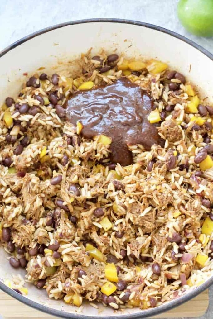 Burrito filling in a pan with a dollop of BBQ sauce.
