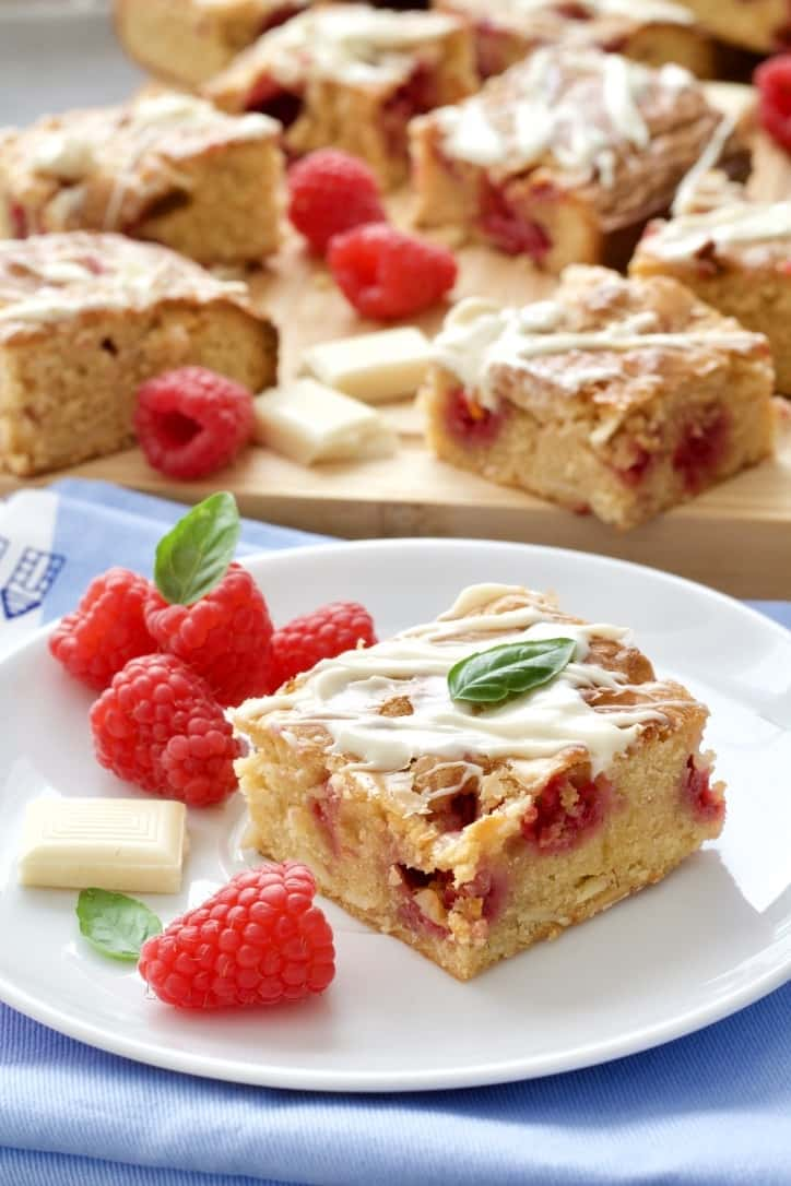 Blondie square on a plate with fresh raspberries.