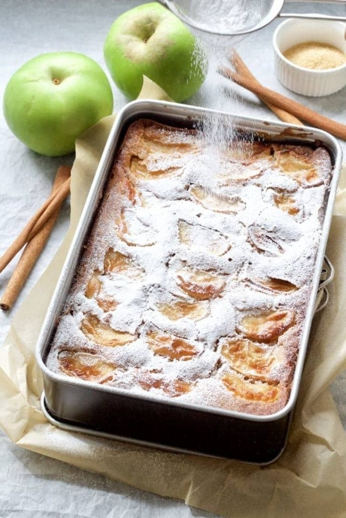 Dorset apple cake sprinkled with icing sugar in a tin.