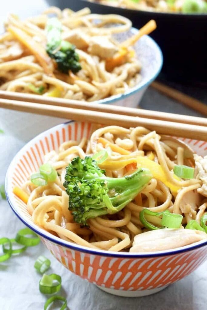Chicken Chow Mein in a bowl close up with broccoli on top.