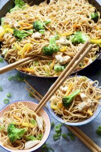 Chicken chow mein in a pan and portions in bowls.