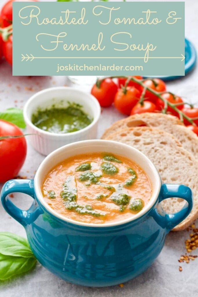 Bowl of tomato & fennel soup with pesto on top, bread slices & tomatoes.