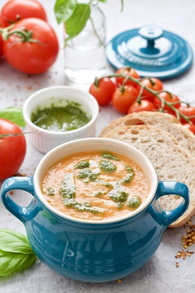 Bowl of tomato & fennel soup with pesto, sliced bread and tomatoes.